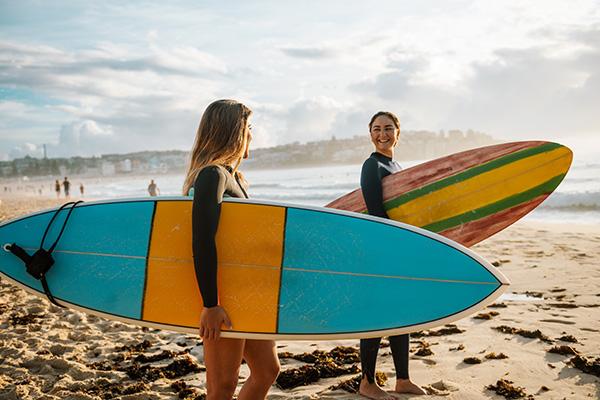 Frauen mit Surfbrettern am Strand - Aktivurlaub Wandern