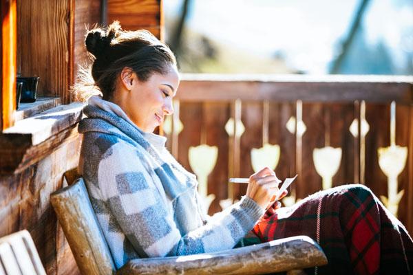 Frau schreibt auf Terrasse - Digital Detox