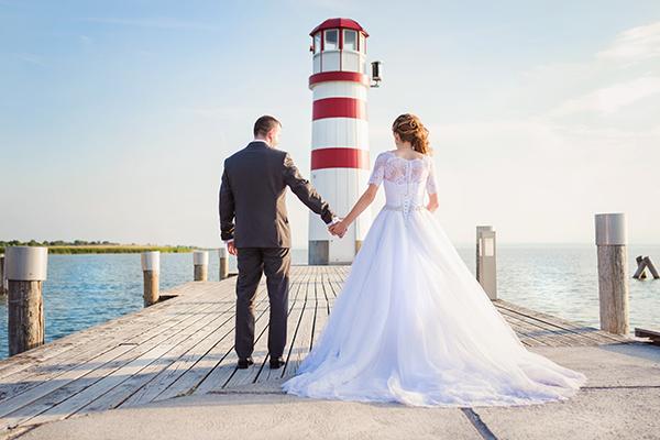 Paar am Steg mit Leuchtturm - Hochzeitslocations