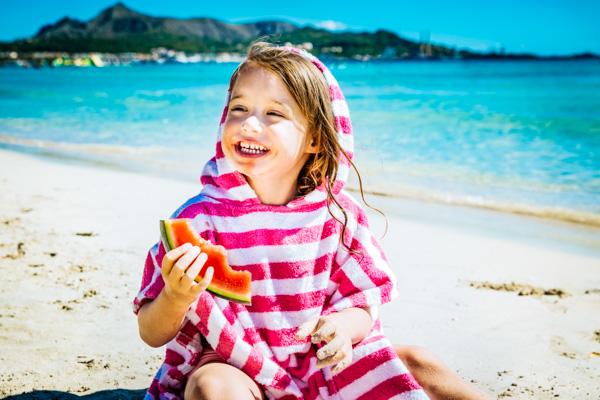 Kind isst Wassermelone am Strand - Familienurlaub auf den Balearen