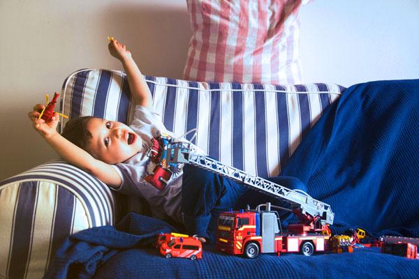 Kind spielt auf dem Sofa - Ferienhaus vs. Hotel