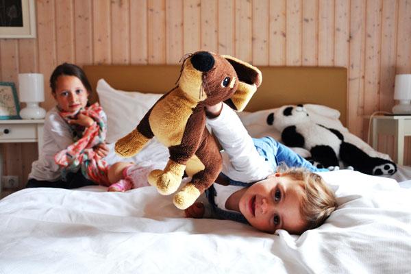 Kinder spielen auf dem Bett - Ferienhaus vs. Hotel