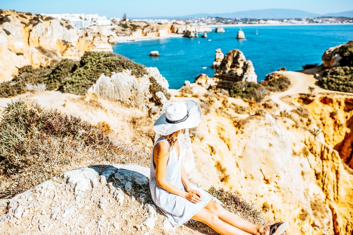 Frau auf den Klippen von Lagos - Roadtrip entlang der Algarve