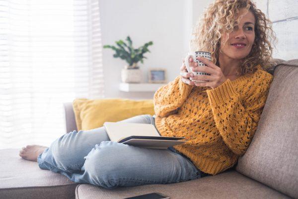 Frau liest auf dem Sofa - Was kann man zuhause machen?