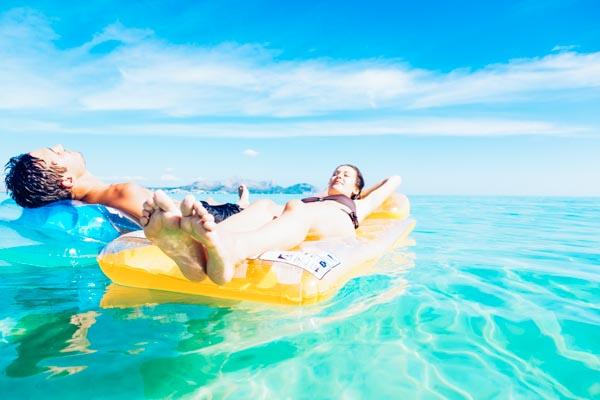 Paar entspannt auf Luftmatratzen - Strandurlaub auf den Balearen