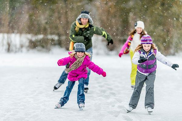 Familie beim Schlittschuhfahren - Weihnachten im Schnee