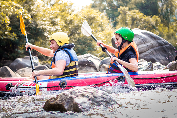 Mann und Frau beim Rafting in Thailand - Reiseziele im Frühling