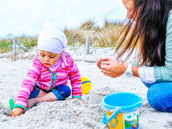 Mutter mit Kleinkind am Strand - Wochenendtrips