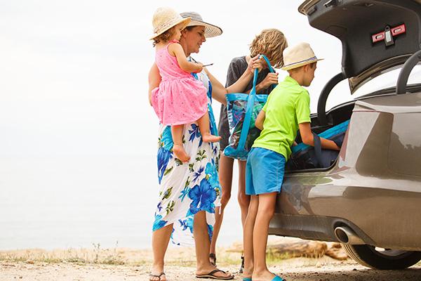 Familie packt Strandsachen ins Auto - Erster Strandurlaub mit Baby