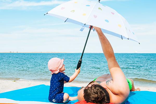 Vater mit Kind unter einem Sonnenschirm - Erster Strandurlaub mit Baby