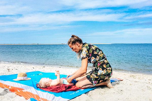 Mutter wickelt Kind am Strand - Erster Strandurlaub mit Baby