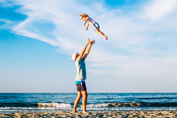 Vater mit Kind am Strand - Familienurlaub an der Adria