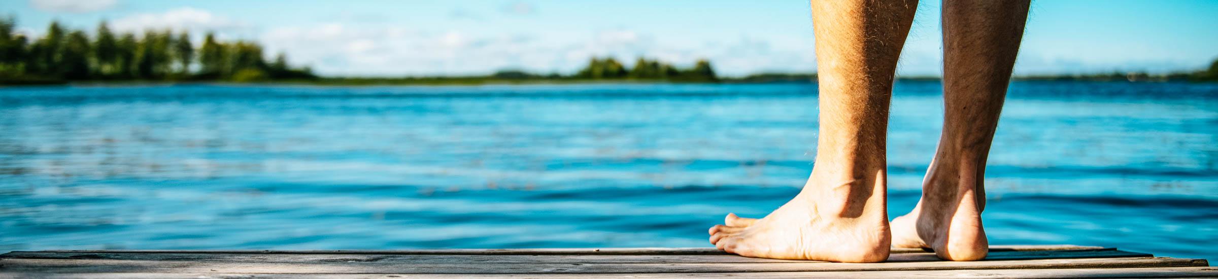 Beine und Füße eines Mannes auf einem Steg am See