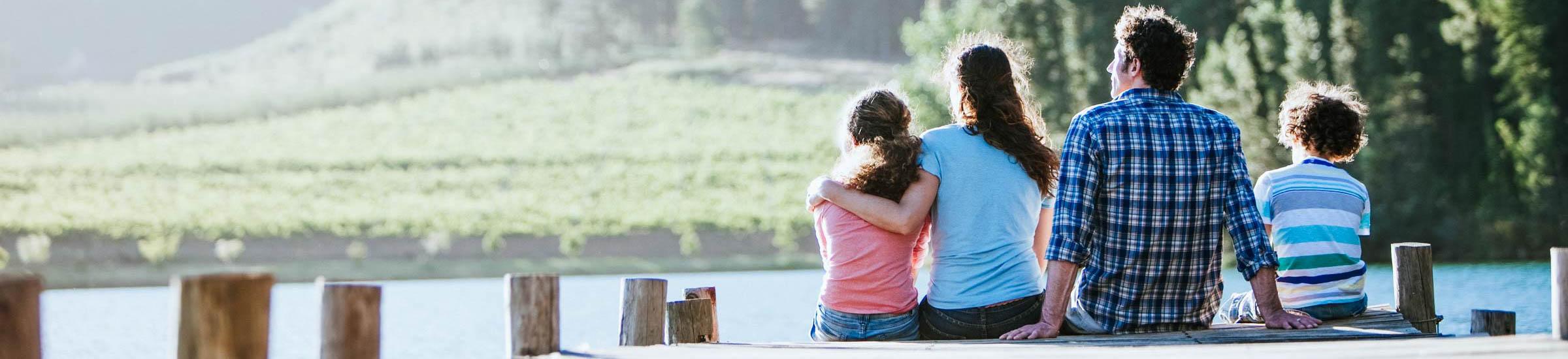 Familie sitzt am Steg eines Sees und genießt ihren Sommerurlaub 2021