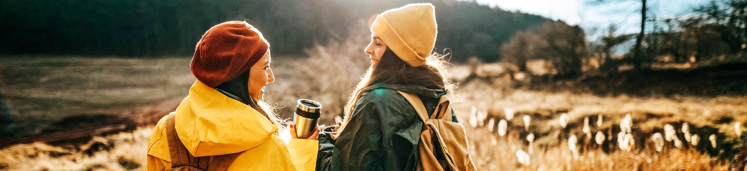 Zwei junge Frauen wandern durch Naturlandschaften – Umweltfreundlich reisen