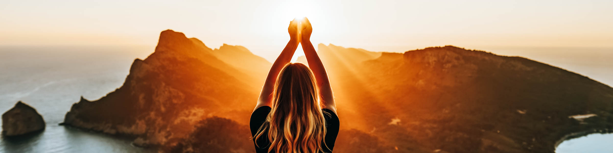 Junge Frau im Sonnenuntergang auf einem Berg mit Blick aufs Meer – Umweltfreundlich reisen