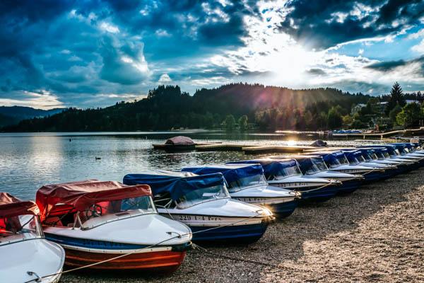Reihe von Motorbooten am Titisee mit Schwarzwald und Sonnenuntergang im Hintergrund