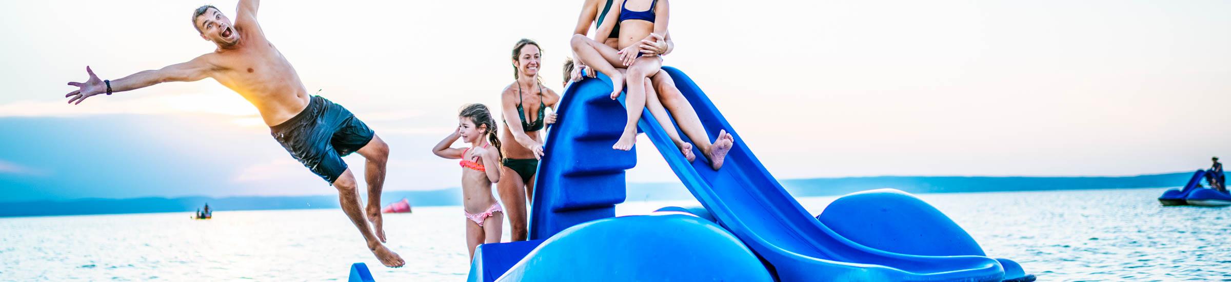 Familienfreundliche Seen Header Desktop: Familie mit fünf Personen hat Spaß auf einem Wasserspielzeug auf dem See