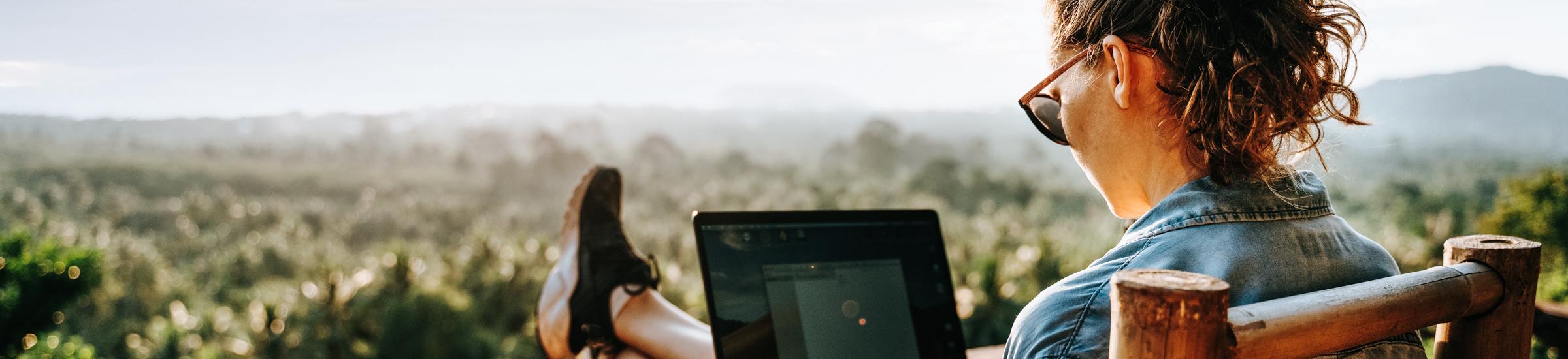 Junge Frau sitzt auf dem Balkon und arbeitet während ihrer Workcation