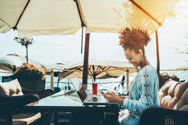Im Urlaub arbeiten: Junge Frau sitzt mit Laptop im Café