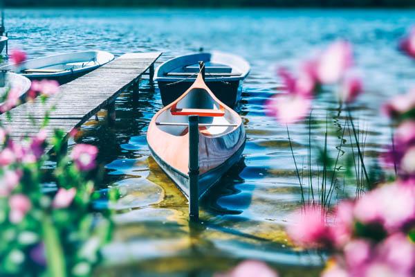Kanus am Steg auf der Müritz, im Vordergrund sieht man verschwommen Blumen
