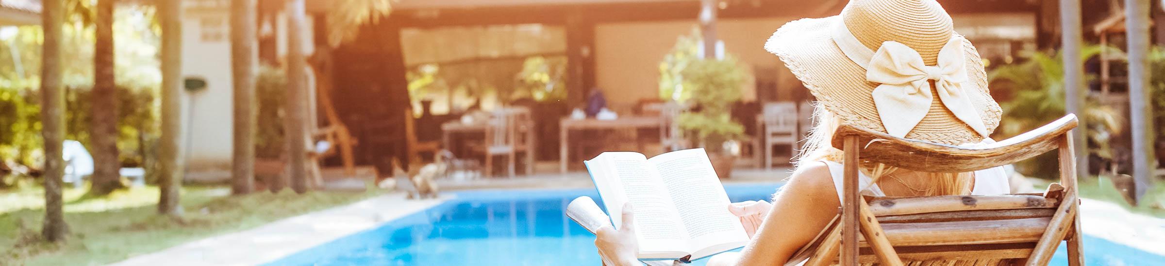Frau liest Buch am Pool mit Ferienhaus im Hintergrund