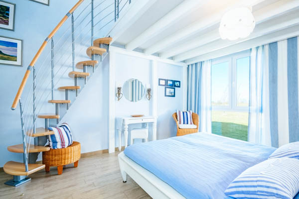 Schlafzimmer mit Treppe zur Galerie im Seepark Ferienhaus Rügen
