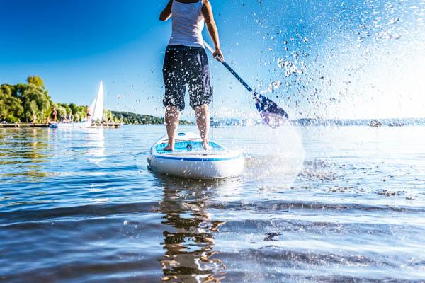 Junger Mann beim Stand-up-Paddeln auf dem Tegernsee