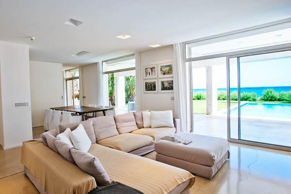 Villa Sal de Mar Wohnbereich mit Couch, Esstisch und Pool im Hintergrund