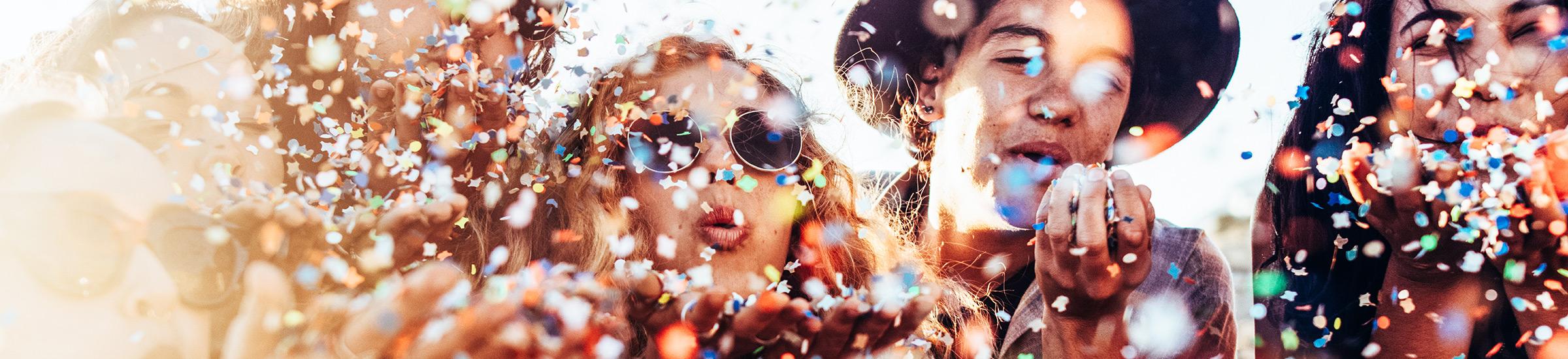 Feiernde Menschen mit Konfetti in bunten Farben