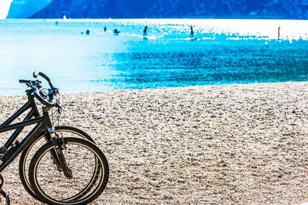 Fahrräder am Strand des Gardasees mit dem See im Hintergrund