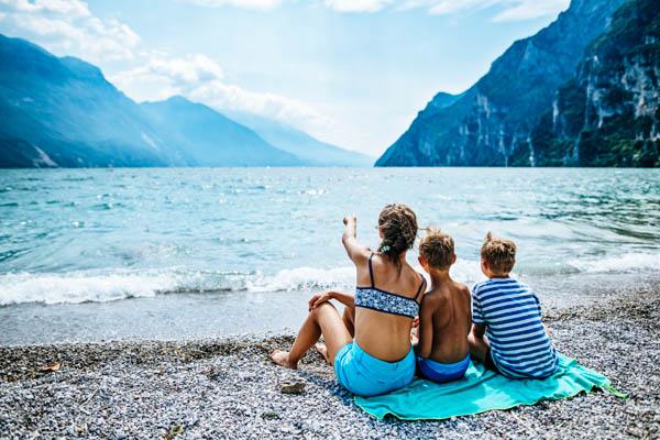 Mutter mit zwei Kindern am Kiesstrand von Riva del Garda