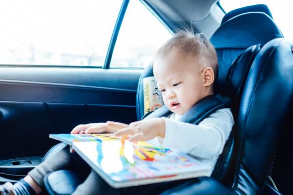 Baby sitzt im Kindersitz im Auto und blättert durch ein Bilderbuch