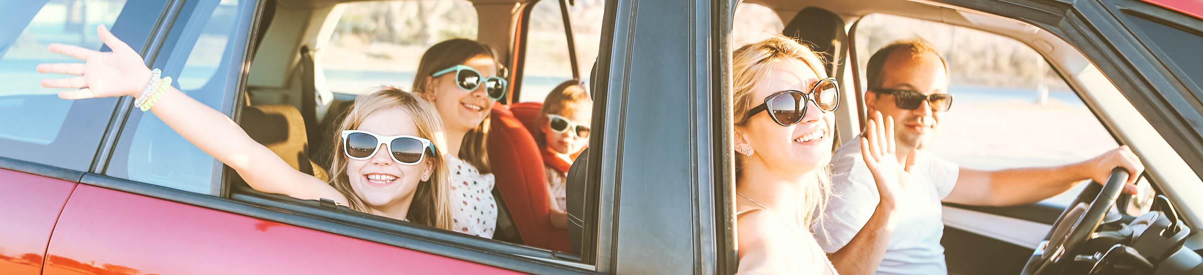 Familie mit drei Kindern winkt in die Kamera – Lange Autofahrt mit Kindern