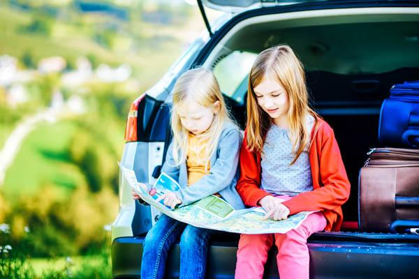 Zwei Kinder sitzen mit einer Landkarte im offenen Kofferraum eines Autos – Lange Autofahrt mit Kindern planen