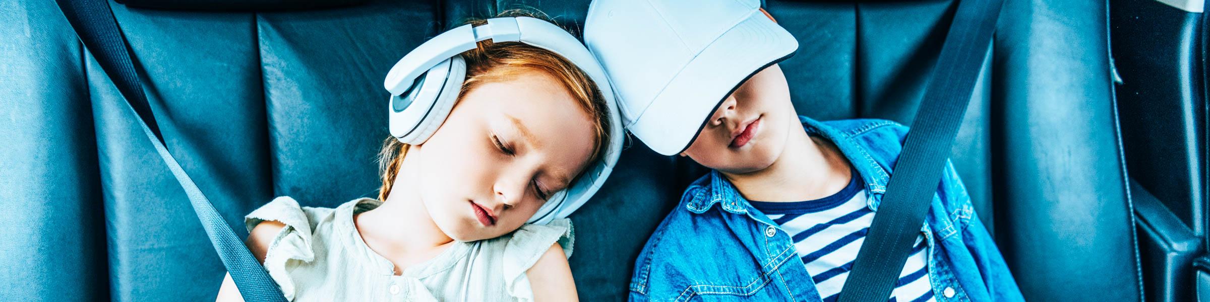 Zwei Kinder schlafen auf der Rückbank eines Autos, das Mädchen trägt Kopfhörer