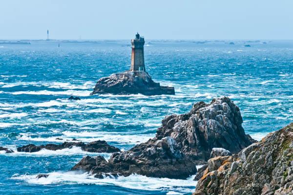 Blick aufs Meer und den Leuchtturm auf einer kleinen Felsinsel am Pointe du Raz in der Bretagne