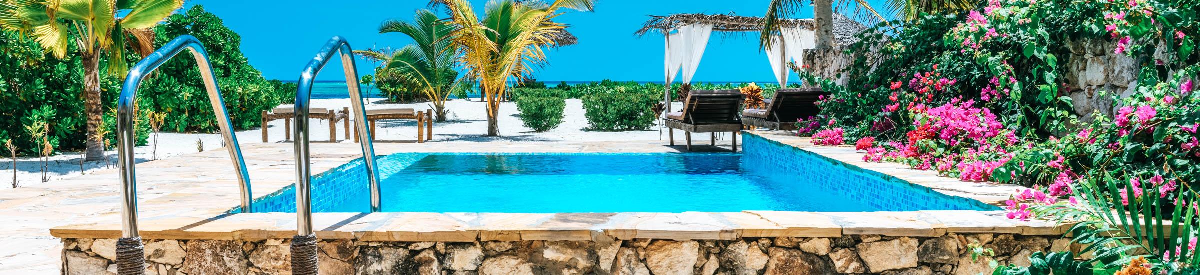 Pool mit Liegewiesen, Palmen und blühenden Büschen