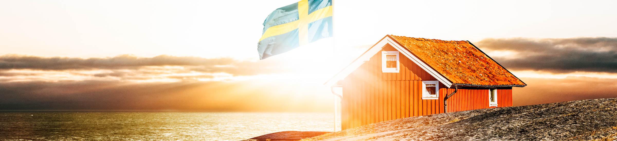 rotes Haus und Schweden-Flagge an der Küste – Familienurlaub in Schweden