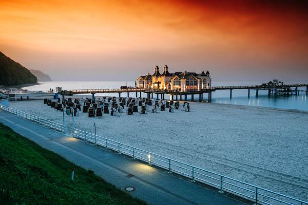 Seebrücke Selling und Strand mit Strandkörbe im Abendrot und Sonnenuntergang - Reisetipps Ostsee