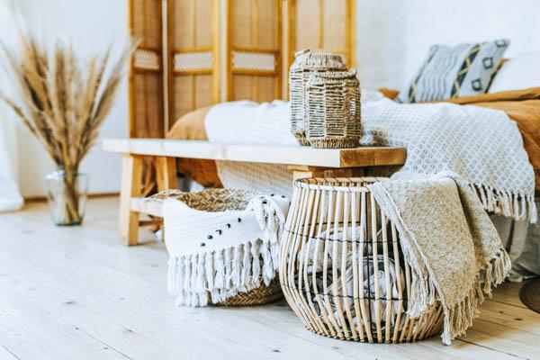 Moderne Einrichtung eines Schlafzimmers mit Bett, Holzbank und verschiedenen Dekorationsgegenständen