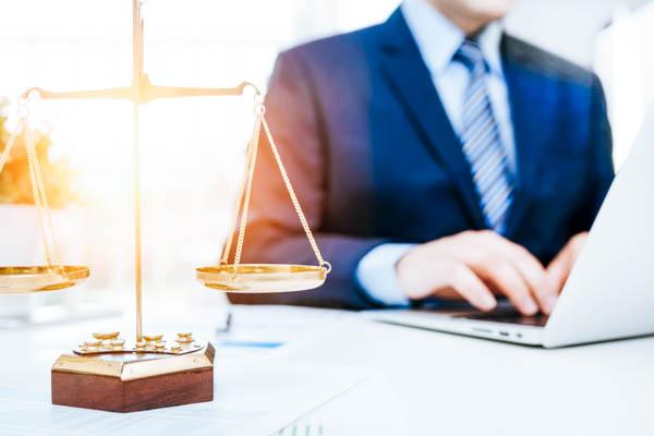 Anwalt arbeitet an seinem Laptop, im Vordergrund steht eine Waage.