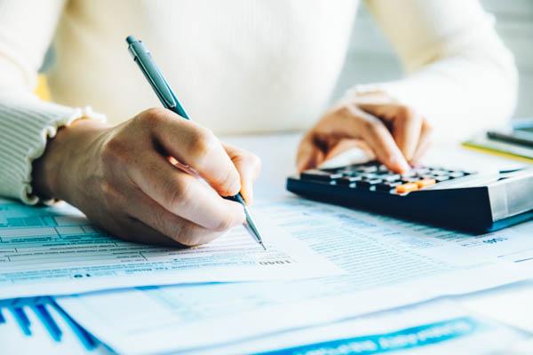Jemand füllt mit einem Kugelschreiber die Steuererklärung aus und benutzt nebenbei einen Taschenrechner.