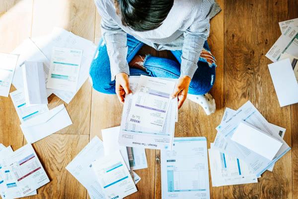 Person sitzt im Schneiderschnitz auf dem Fußboden und ist von Rechnungen und Papierkram umgeben